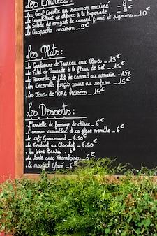 Tablero del menú en la pared exterior de un restaurante en parís.