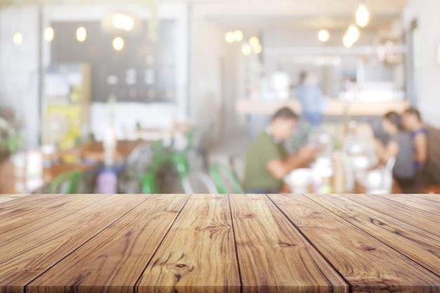 Tablero de mesa de madera en blanco con personas en el restaurante o en el fondo de cafetería de café para producto de montaje