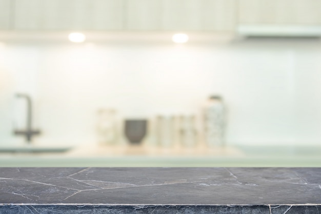 Tablero de mesa de piedra de mármol negro vacío e interior de cocina borrosa