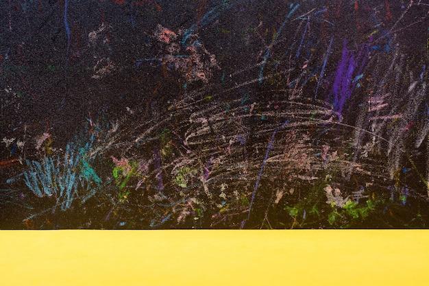Tablero negro abstracto pintado con lápices de colores y mesa amarilla