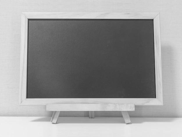 Tablero negro de madera del primer en el escritorio de madera en tono blanco y negro