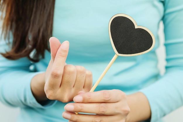 Tablero negro de madera del primer en forma del corazón con el finger de la mujer en mini símbolo del corazón