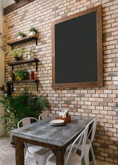 Tablero negro vacío en la pared de ladrillo y mesa de comedor en la parte inferior.