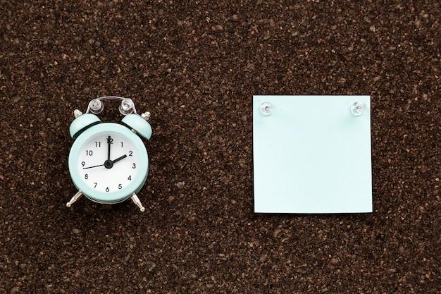 Tablero de notas con pegatinas vacías y reloj para estudiar o trabajar. tenga en cuenta los documentos para su mensaje con un botón pulsador transparente.