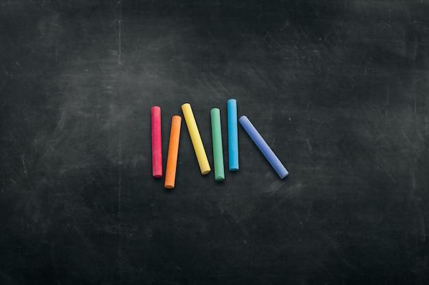 Tablero oscuro con crayones de colores para dibujar el fondo