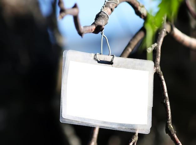 Tablero de papel blanco vacío colgando de la rama de un árbol