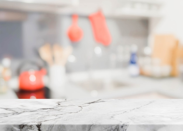 Tablero de piedra blanca y fondo interior borroso de la cocina - puede utilizado para la exhibición o el montaje de sus productos.