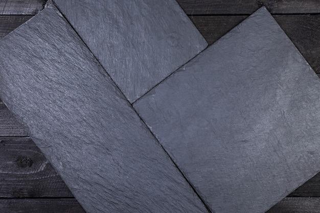 Tablero de piedra pizarra en la mesa de madera oscura.