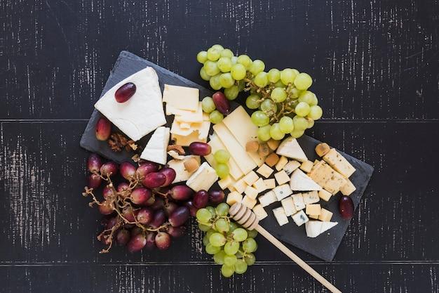 Tablero de pizarra negro con uvas rojas y verdes con diferentes tipos de rebanadas de queso y cubos sobre fondo negro