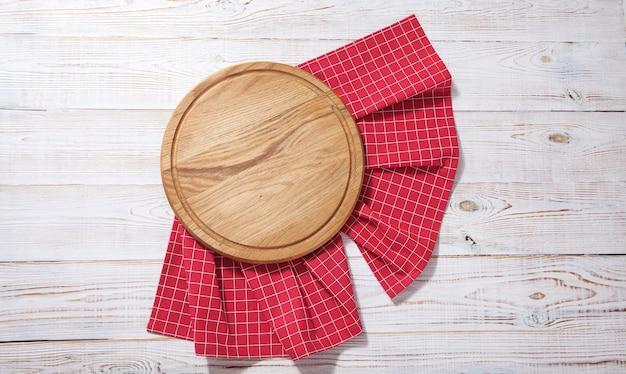 Tablero de pizza vacía y toalla roja sobre cubierta de madera blanca