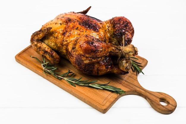 Tablero con pollo y romero en blanco