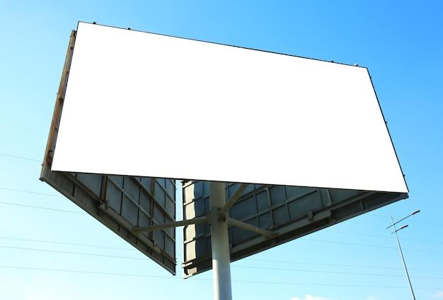 Tablero de publicidad en blanco al aire libre contra el cielo azul