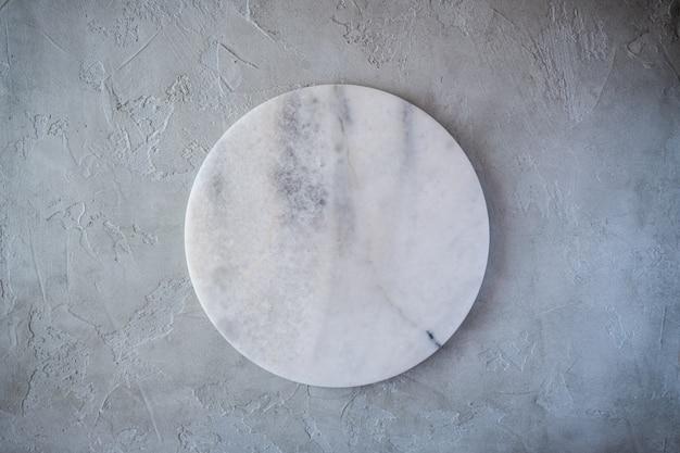Tablero redondo de textura de mármol vacía blanca sobre fondo gris. vista superior. copia espacio
