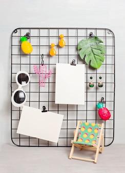 Tablero de rejilla de alambre con accesorios y tarjetas para citas inspiradoras.