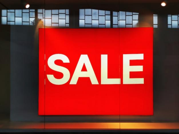 Tablero rojo grande iluminado con texto de venta en blanco en una tienda minorista