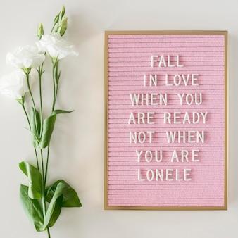 Tablero rosa con texto y flores.
