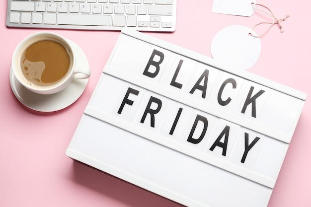 Tablero con texto black friday, taza de café y computadora en la superficie de color