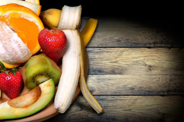 Tablero vintage con frutas, naranja, kiwi, plátano, fresa y aguacate, vista superior