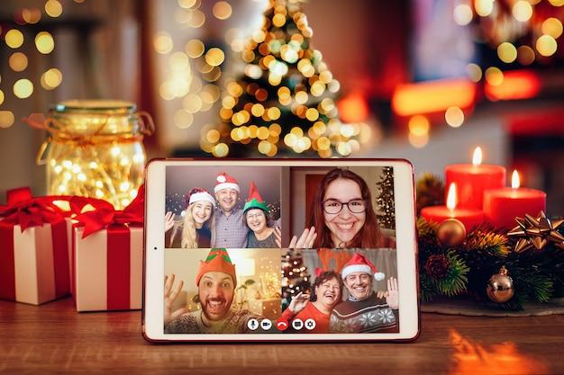 Tablet en una acogedora habitación con una videollamada navideña con la familia. concepto de familias en cuarentena durante la navidad por el coronavirus