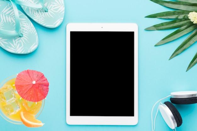 Tablet y cosas de verano sobre fondo de color