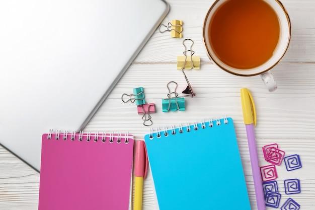Tablet pc, cuadernos y taza de té en madera blanca