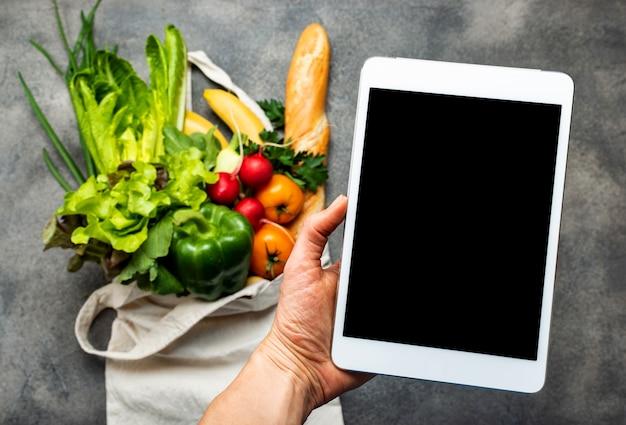 Tablet pc con pantalla en blanco en la mano femenina sobre la bolsa de compras llena de alimentos saludables.