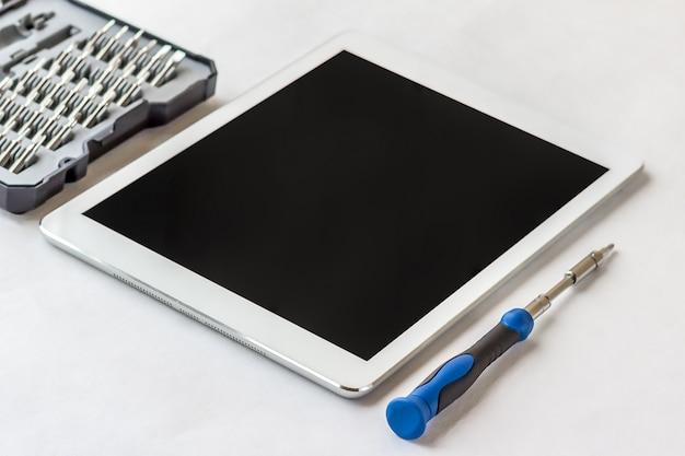 Tablet pc con pantalla vacía y herramientas, destornillador closeup