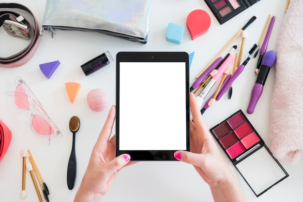 Tablet rodeada de maquillaje