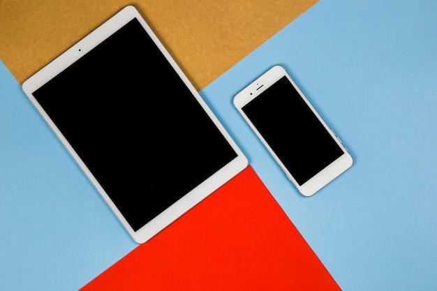 Tablet con smartphone en mesa luminosa