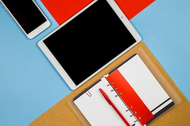 Tablet con smartphone y notebook en mesa luminosa