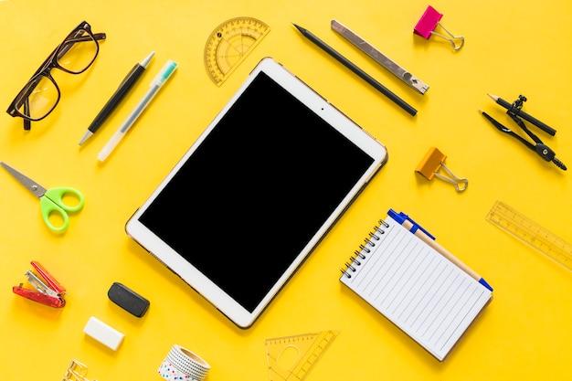 Tableta con accesorios de oficina en mesa.