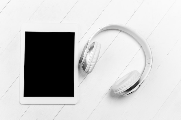 Tableta y auriculares. pantalla en blanco. composición monocromática elegante y moderna en color blanco en la pared del estudio. vista superior, endecha plana.