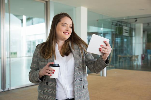 Tableta y bebida sonrientes de la tenencia de la mujer de negocios al aire libre