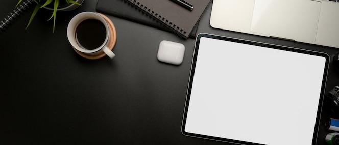 Tableta en blanco en el espacio de trabajo con taza de café y útiles de oficina