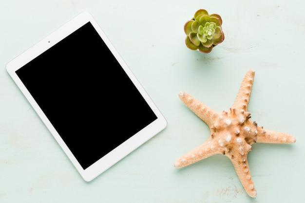 Tableta en blanco con estrellas de mar en superficie ligera