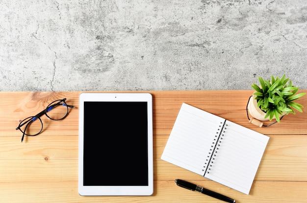 Tableta en blanco con ordenador portátil, gafas y cactus en la mesa de madera
