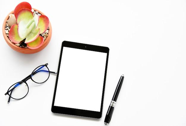 Tableta en blanco, plantas suculentas y cactus, pluma en el escritorio