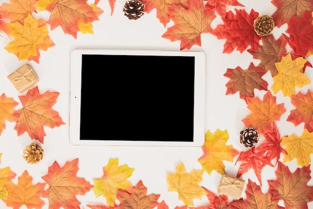 Tableta en blanco vista superior decorada con coloridas hojas de otoño de arce y cajas de regalo