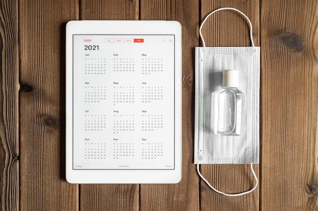 Una tableta con un calendario abierto para el año 2021 y máscara médica protectora y desinfectante de manos sobre un fondo de mesa de tablas de madera. concepto de protección contra el coronavirus covid-19 en 2021.