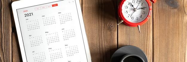Una tableta con un calendario abierto para el año 2021, una taza de café y un despertador rojo sobre un fondo de tabla de tablas de madera
