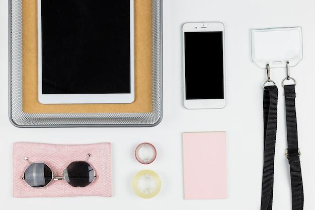 Tableta cerca de teléfono inteligente, gafas de sol, papel y etiqueta con su nombre