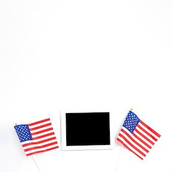 Tableta colocada entre banderas americanas.