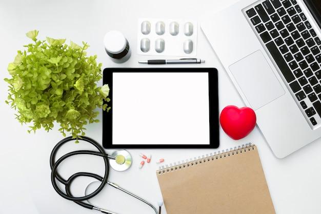 Tableta, cuaderno, computadora portátil, frasco de medicina, bolígrafo con estetoscopio