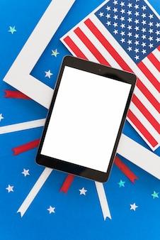 Tableta y decoración navideña del día de la independencia sobre fondo azul.