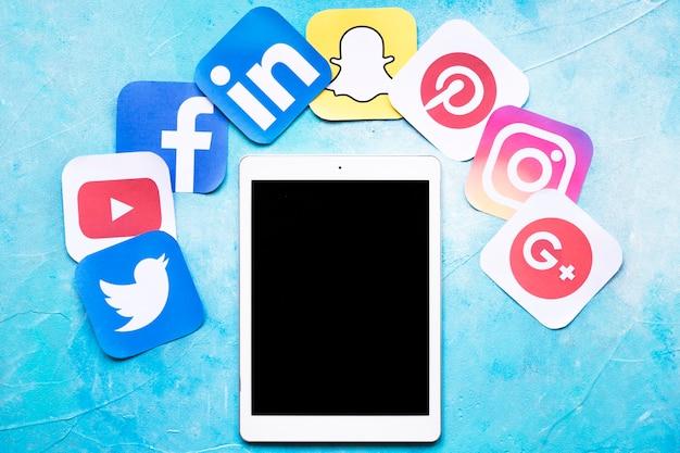 Tableta digital alrededor de coloridos iconos de redes sociales sobre fondo azul pintado