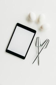 Tableta digital con batidor y huevos sobre fondo blanco.