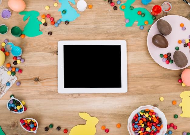 Tableta digital en blanco rodeada de caramelos de gemas de colores; huevos de pascua; conejito de papel recortado en mesa de madera