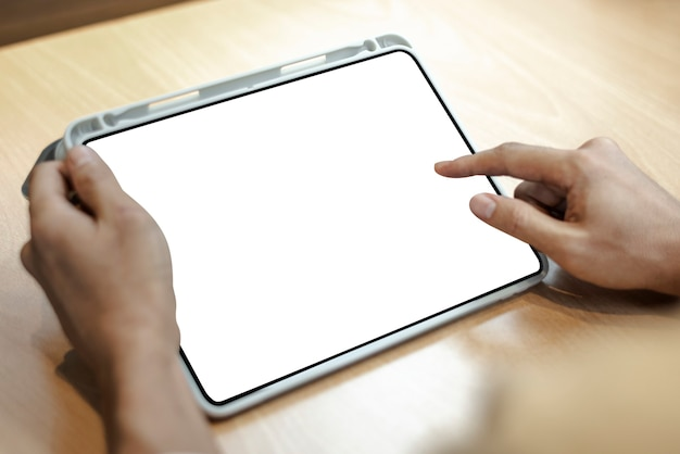 Tableta digital en blanco sobre una mesa de madera clara