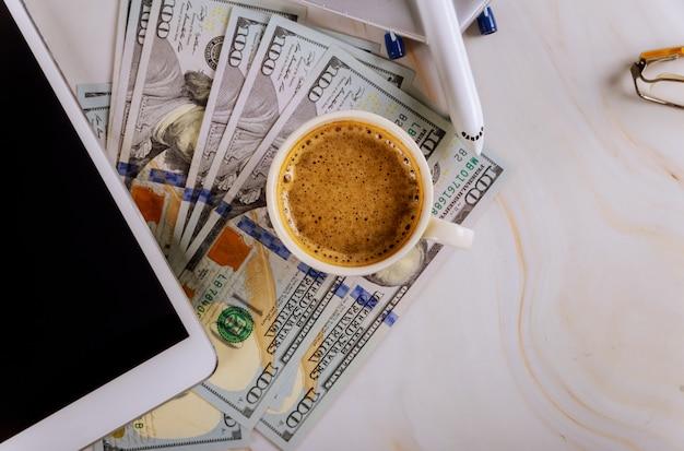 Tableta digital con la compra de billetes de avión en los billetes de dólar estadounidense, con una taza de café de viaje de vacaciones en avión.