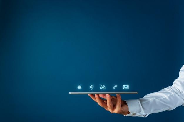 Tableta digital con contactos de interfaz brillante e iconos de información que salen de ella